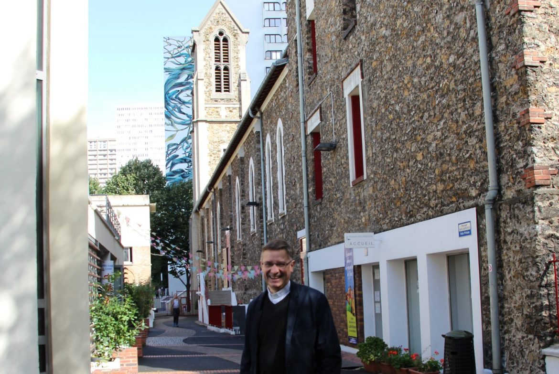 Le père Philippe Capelle, curé de Saint-Hippolyte, devant le clocher de l'église.
