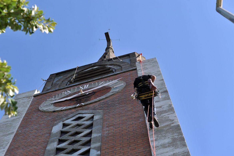 Un ouvrier escalade le clocher de l'église Saint-Stanislas-des-Blagis.