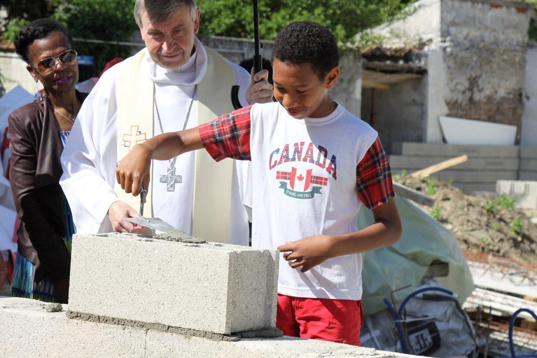enfant évêque pose pierre