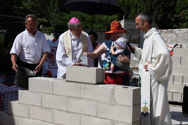 femme évêque pose pierre