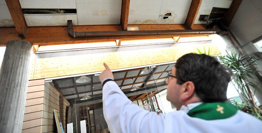 Le curé montre les dommages de la toiture de l'église Sainte-Marie-des-Pauples à Cergy-Le-Haut