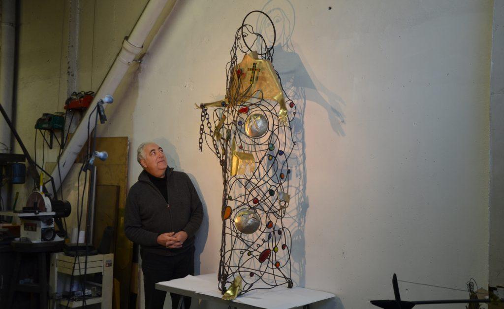 Jean-Charles Detallante regardant sa statue de sainte Bathilde dans son atelier.